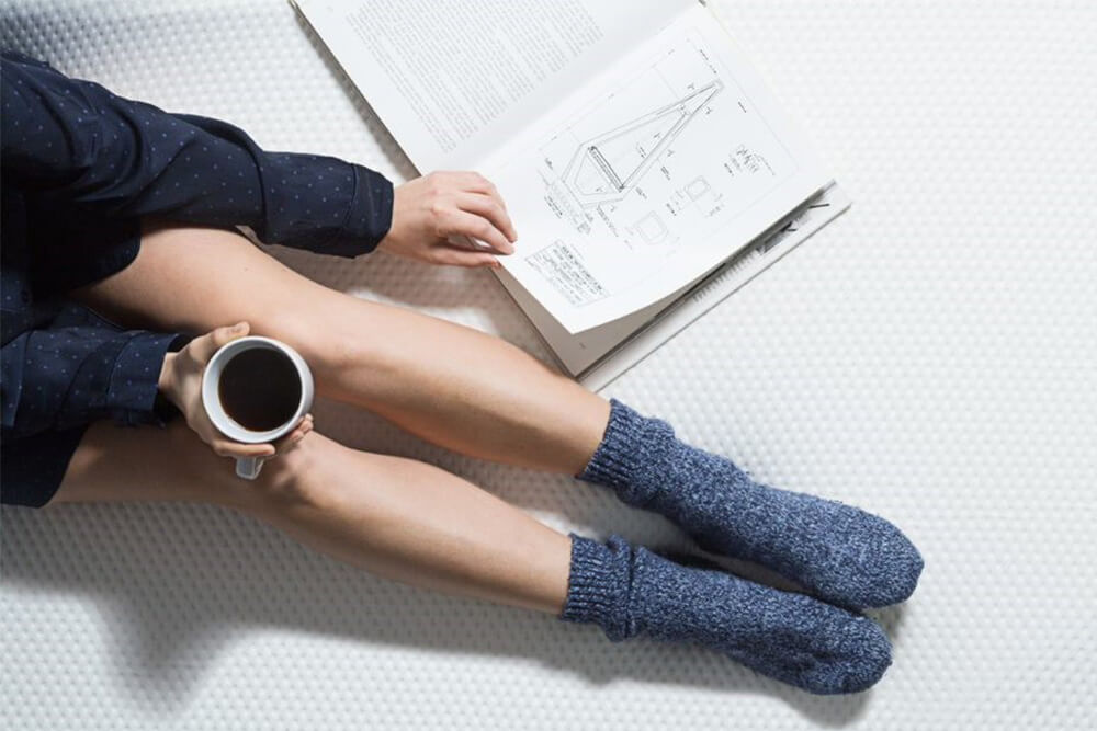 Girl sitting on bed with coffee and notebook
