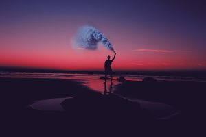The silhouette of a man at sunset, holding a smoke canister releasing blue smoke into the night