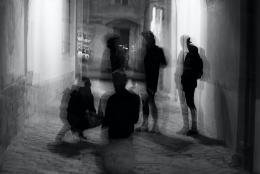 Dark figures stand ominously in a black and white alley