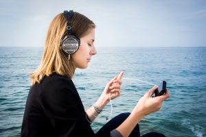 Woman with headphones sits relaxed near the ocean.