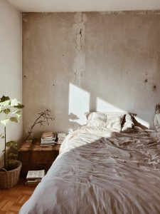 Stylish made bed in room with sunlight coming in